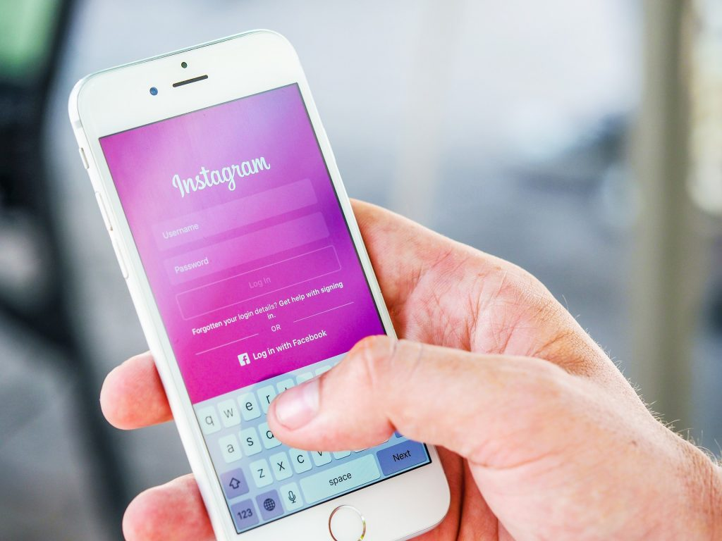 Person holding phone displaying Instagram login screen