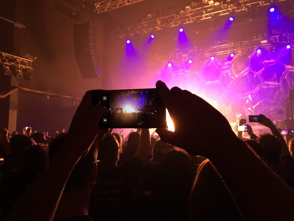 a person filming a concert on a smartphone