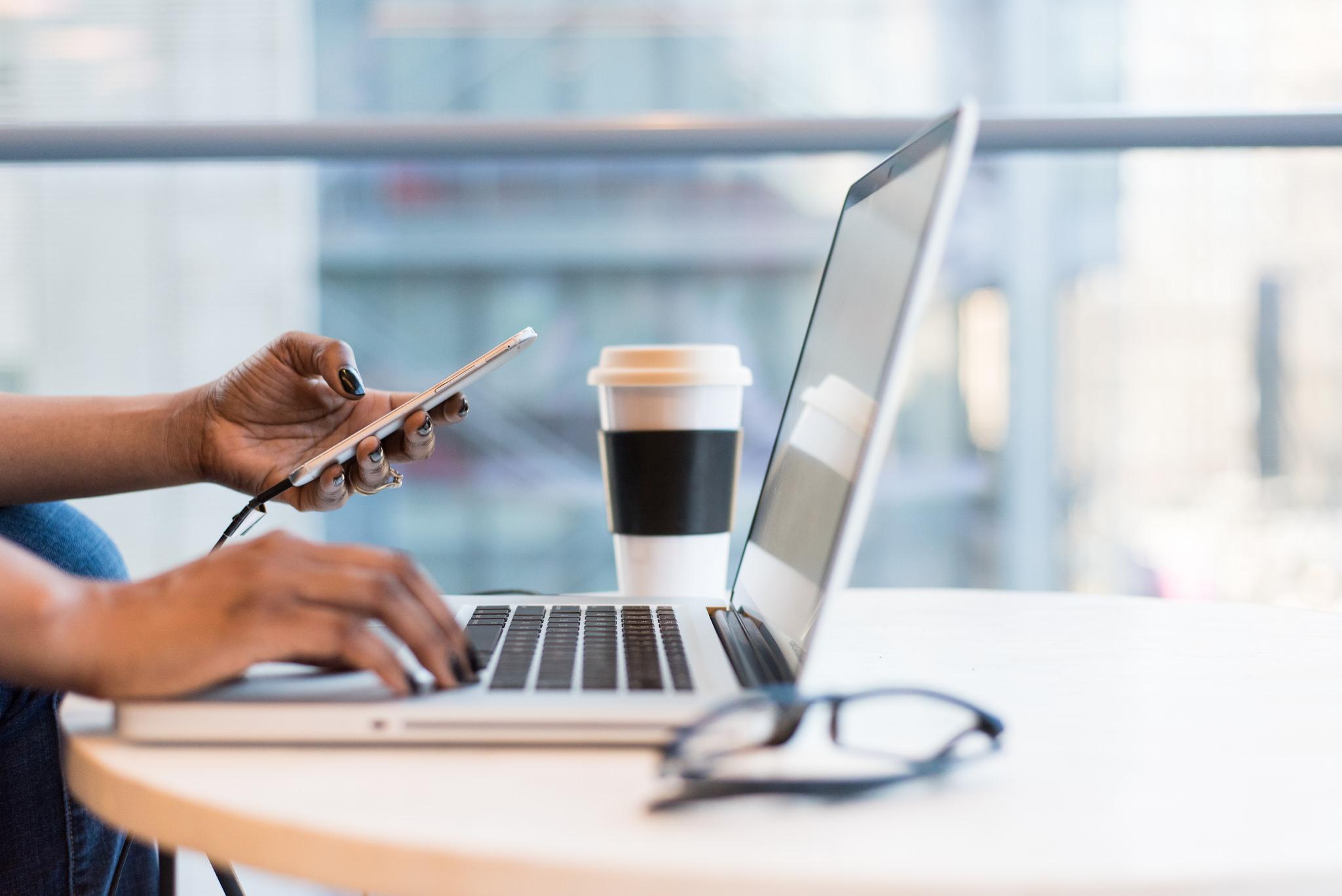 Black woman working at Macbook computer